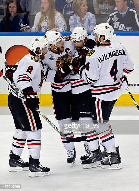 Patrick Sharp of the Chicago Blackhawks celebrates with teammates Niklas Hjalmarsson Duncan Keith and Jonathan Toews after scoring an empty net goal...
