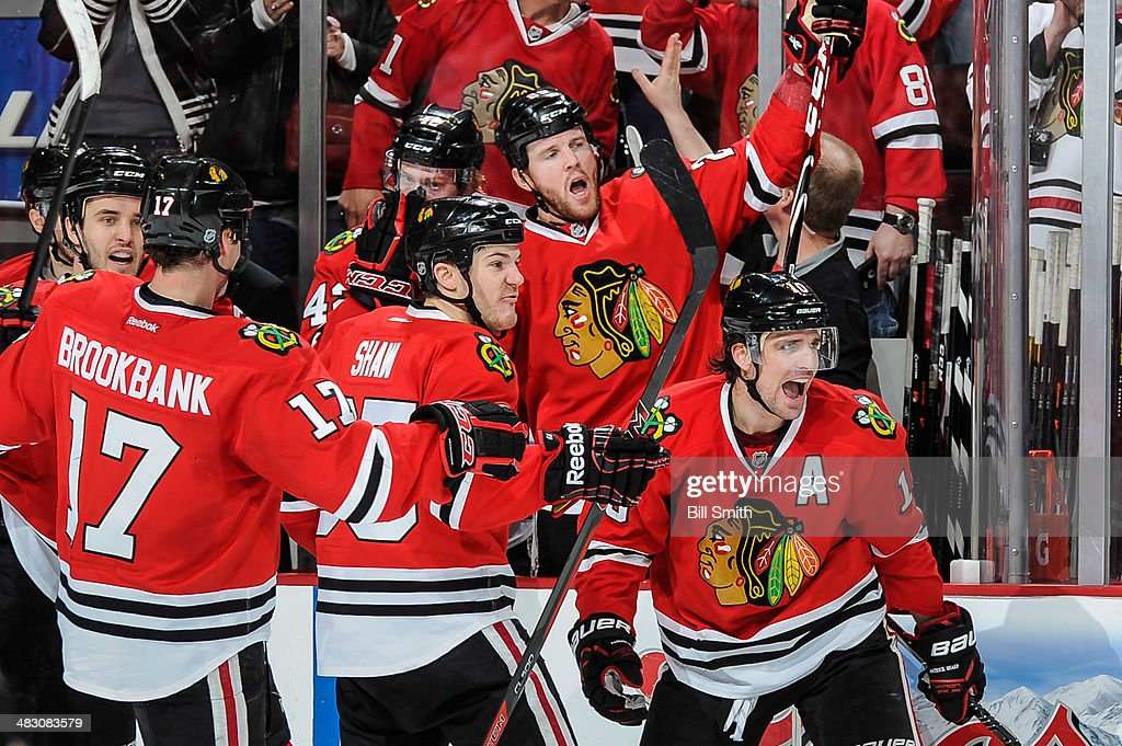 Patrick Sharp #10 of the Chicago Blackhawks celebrates with teammates including Niklas Hjalmarsson #4, Andrew Shaw #65 and Bryan Bickell #29 after scoring against the St. Louis Blues in the second period during the NHL game on April 06, 2014 at the United Center in Chicago, Illinois.