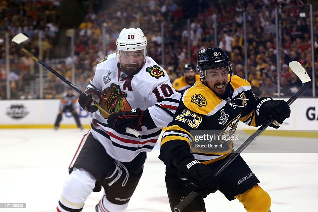 Patrick Sharp #10 of the Chicago Blackhawks checks Chris Kelly #23 of the Boston Bruins in Game Six of the 2013 NHL Stanley Cup Final at TD Garden on June 24, 2013 in Boston, Massachusetts.