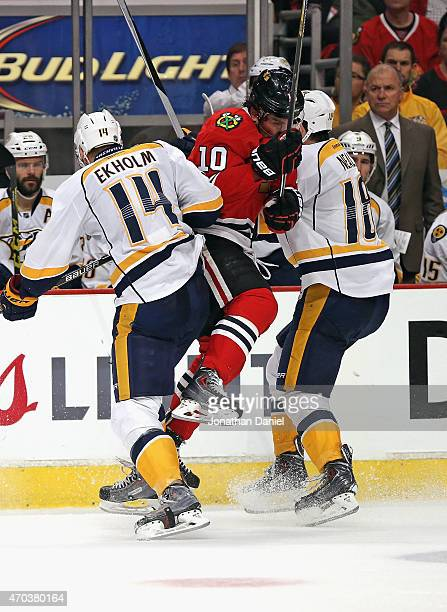 Patrick Sharp of the Chicago Blackhawks collides with Mattias Ekholm and James Neal of the Nashville Predators in Game Three of the Western...