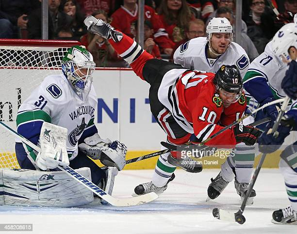 Patrick Sharp of the Chicago Blackhawks falls to the ice between Eddie Lack and Christopher Tanev of the Vancouver Canucks at the United Center on...
