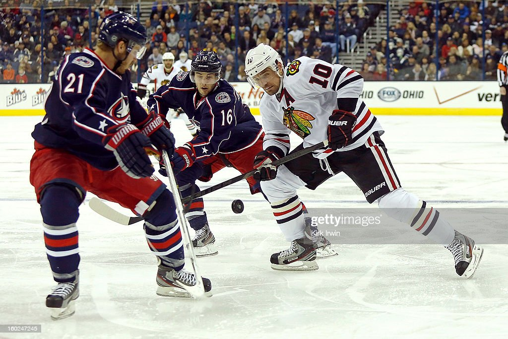 Patrick Sharp #10 of the Chicago Blackhawks flips the puck past James Wisniewski #21 of the Columbus Blue Jackets and Derick Brassard #16 of the Columbus Blue Jackets on January 26, 2013 at Nationwide Arena in Columbus, Ohio.