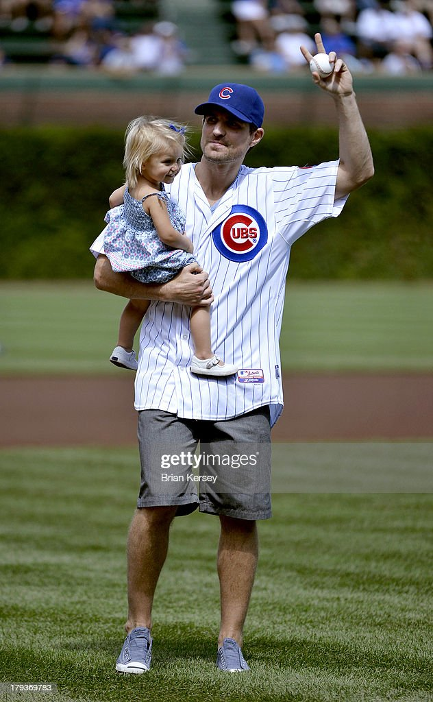 Patrick Sharp #10 of the Chicago Blackhawks holds his daughter Madelyn as he waves to the crowd before throwing out a ceremonial first pitch before the game between the Miami Marlins and the Chicago Cubs at Wrigley Field on September 2, 2013 in Chicago, Illinois.