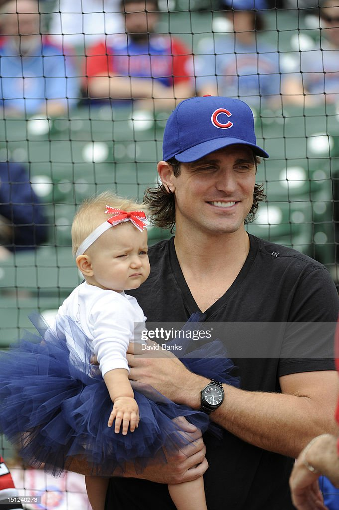 Patrick Sharp of the Chicago Blackhawks holds his daughter Madelyn Sharp before throwing out the first pitch before the game between the Chicago Cubs and the San Francisco Giants on September 2, 2012 at Wrigley Field in Chicago, Illinois.
