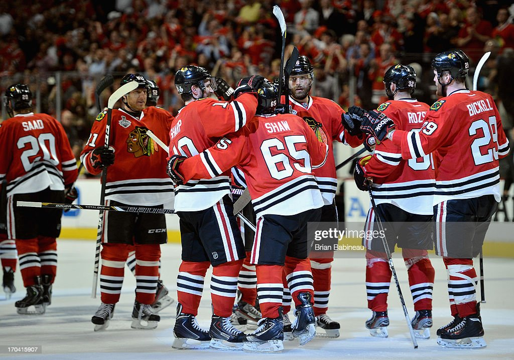 Patrick Sharp #10 of the Chicago Blackhawks hugs teammate Andrew Shaw #65 after Shaw scored the game-winning goal during the third overtime of Game One of the 2013 Stanley Cup Final to beat the Boston Bruins 4-3 at the United Center on June 12, 2013 in Chicago, Illinois.