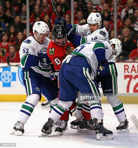 Patrick Sharp of the Chicago Blackhawks is defended by Bo Horvat Kevin Bieksa and Luca Sbisa of the Vancouver Canucks at the United Center on April 2...