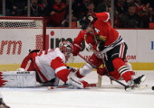 Patrick Sharp of the Chicago Blackhawks is pushed into Jimmy Howard of the Detroit Red Wings by Brad Stuart at the United Center on February 21 2012...