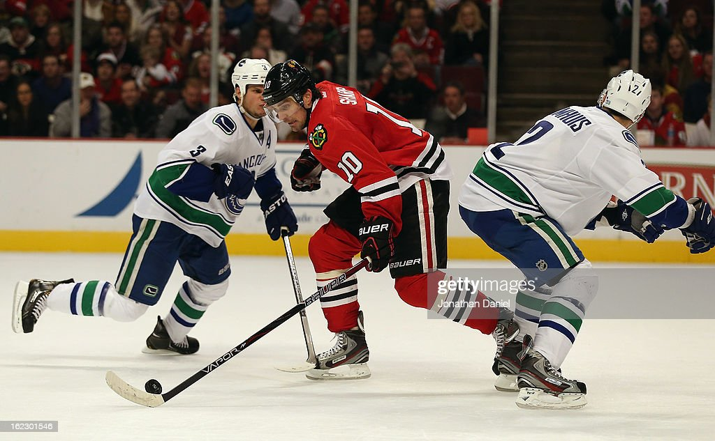 <a gi-track='captionPersonalityLinkClicked' href=/galleries/search?phrase=Patrick+Sharp&family=editorial&specificpeople=206279 ng-click='$event.stopPropagation()'>Patrick Sharp</a> #10 of the Chicago Blackhawks moves between <a gi-track='captionPersonalityLinkClicked' href=/galleries/search?phrase=Kevin+Bieksa&family=editorial&specificpeople=688792 ng-click='$event.stopPropagation()'>Kevin Bieksa</a> #3 and <a gi-track='captionPersonalityLinkClicked' href=/galleries/search?phrase=Dan+Hamhuis&family=editorial&specificpeople=204213 ng-click='$event.stopPropagation()'>Dan Hamhuis</a> #2 of the Vancouver Canucks at the United Center on February 19, 2013 in Chicago, Illinois. The Blackhawks defeated the Canucks 4-3 in a shootout.