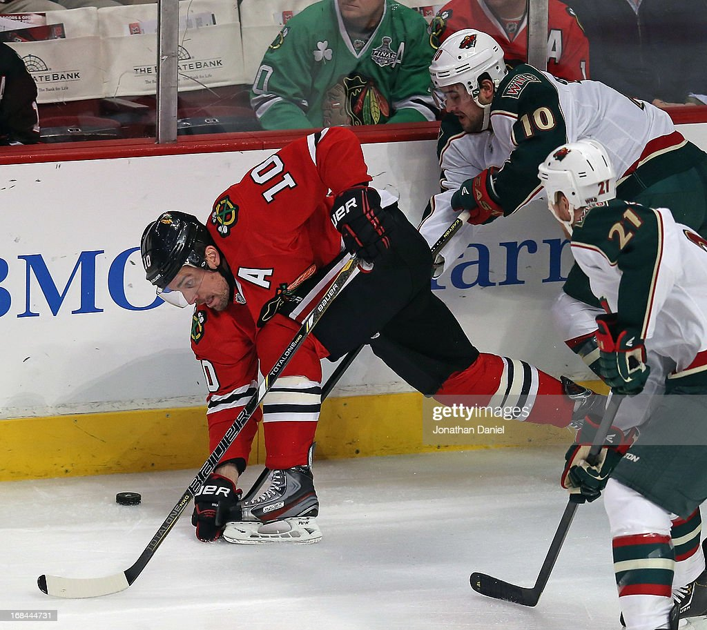 Patrick Sharp #10 of the Chicago Blackhawks tries to control the puck under pressure from Devin Setoguchi #10 and Kyle Bordziak #21 of the Minnesota Wild in Game Five of the Western Conference Quarterfinals during the 2013 NHL Stanley Cup Playoffs at the United Center on May 9, 2013 in Chicago, Illinois.