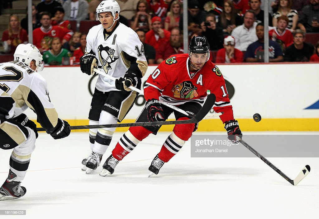 Patrick Sharp #10 of the Chicago Blackhawks tries to knock down the puck between Chuck Kobasew #12 and Chris Kunitz #14 of the Pittsburgh Penguins during an exhibition game at United Center on September 19, 2013 in Chicago, Illinois.