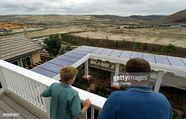 Patrick Sullivan with his son Timothy both of Westchester look over the solar–paneled backyard trellace and views of new home construction from the...