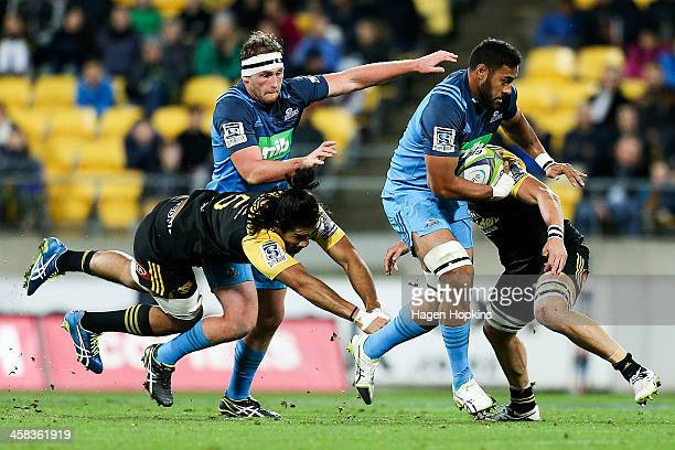 Patrick Tuipulotu of the Blues is tackled by Michael Fatialofa and Brad Shields of the Hurricanes during the round 15 Super Rugby match between the...