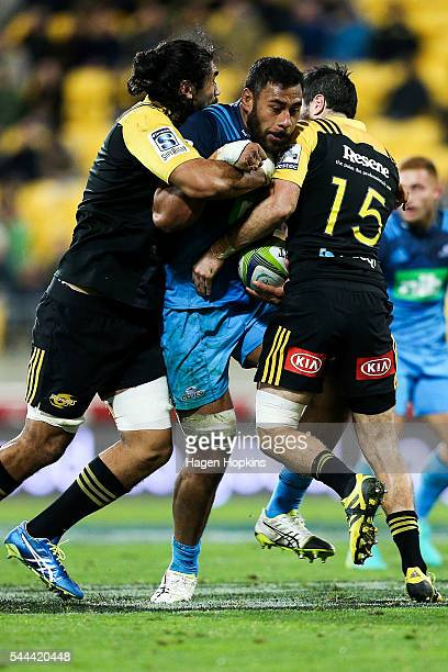 Patrick Tuipulotu of the Blues is tackled by Michael Fatialofa and James Marshall of the Hurricanes during the round 15 Super Rugby match between the...