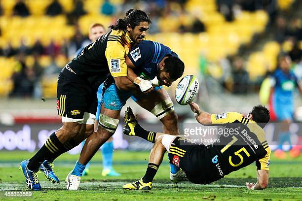 Patrick Tuipulotu of the Blues loses the ball in the tackle of Michael Fatialofa and James Marshall of the Hurricanes during the round 15 Super Rugby...