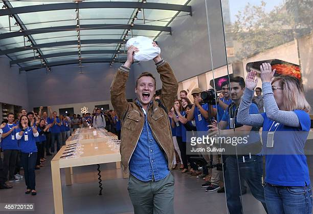 Patrick Tuntland holds up his new iPhone 6 Plus as he leaves an Apple Store on September 19 2014 in Palo Alto California Hundreds of people lined up...