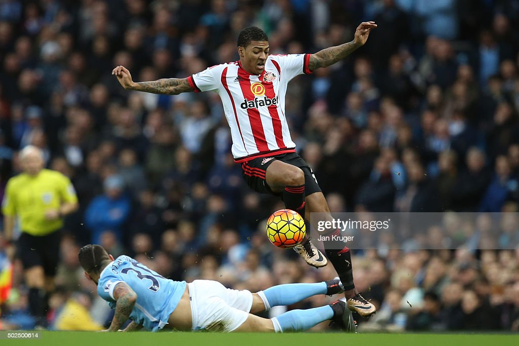 Patrick Van Aanholt of Sunderland is tackled by Nicolas Otamendi of Manchester City during the Barclays Premier League match between Manchester City...