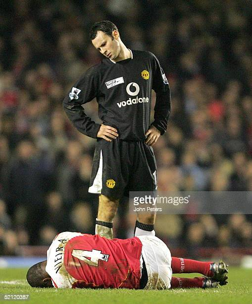Patrick Vieira of Arsenal lies on the ground while Ryan Giggs of Manchester United looks down at him during the Barclays Premiership match between...