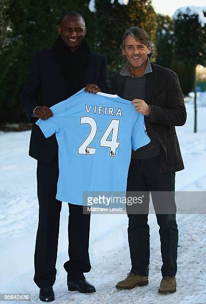 Patrick Vieira poses with his new manager Roberto Mancini as he signs for Manchester City during a photocall at their Carrington Training Ground on...