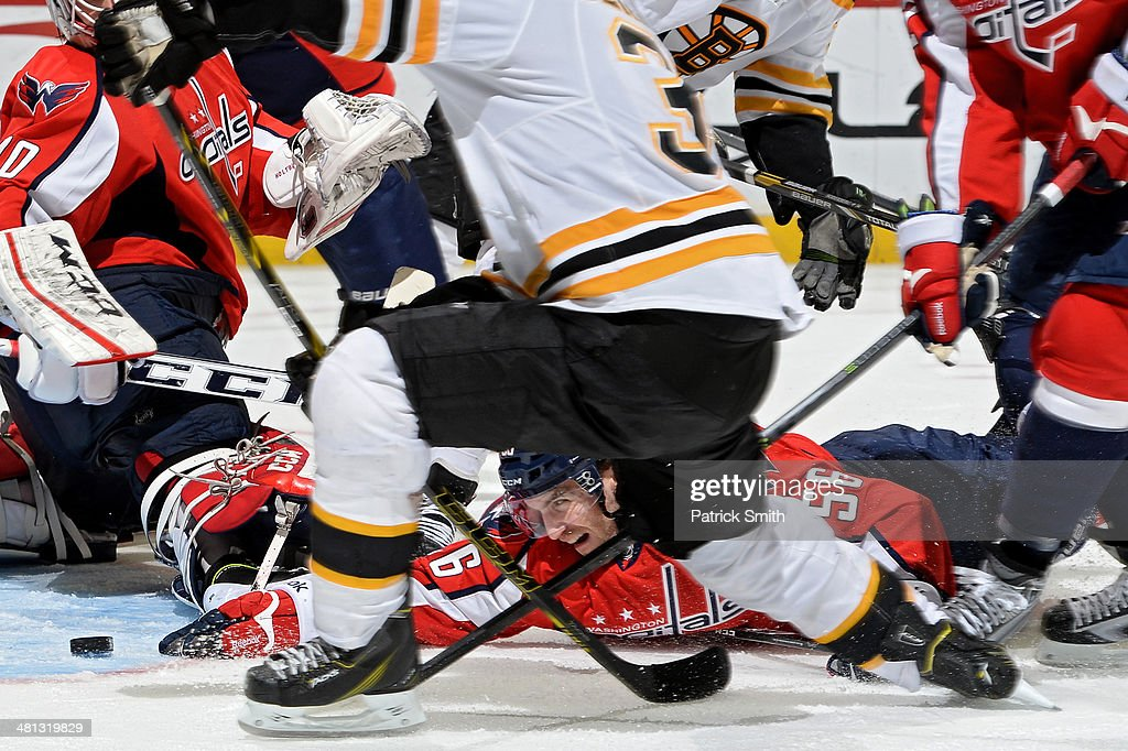 Patrick Wey #56 of the Washington Capitals dives and reaches for the puck in attempt to stop a goal by Patrice Bergeron #37 of the Boston Bruins in the third period during an NHL game at Verizon Center on March 29, 2014 in Washington, DC. The Boston Bruins won, 4-2.