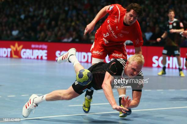 Patrick Wiencek of Germany is challenged by Jonathan Stenbacken of Melsungen during a benefit match between the German national handball team and MT...