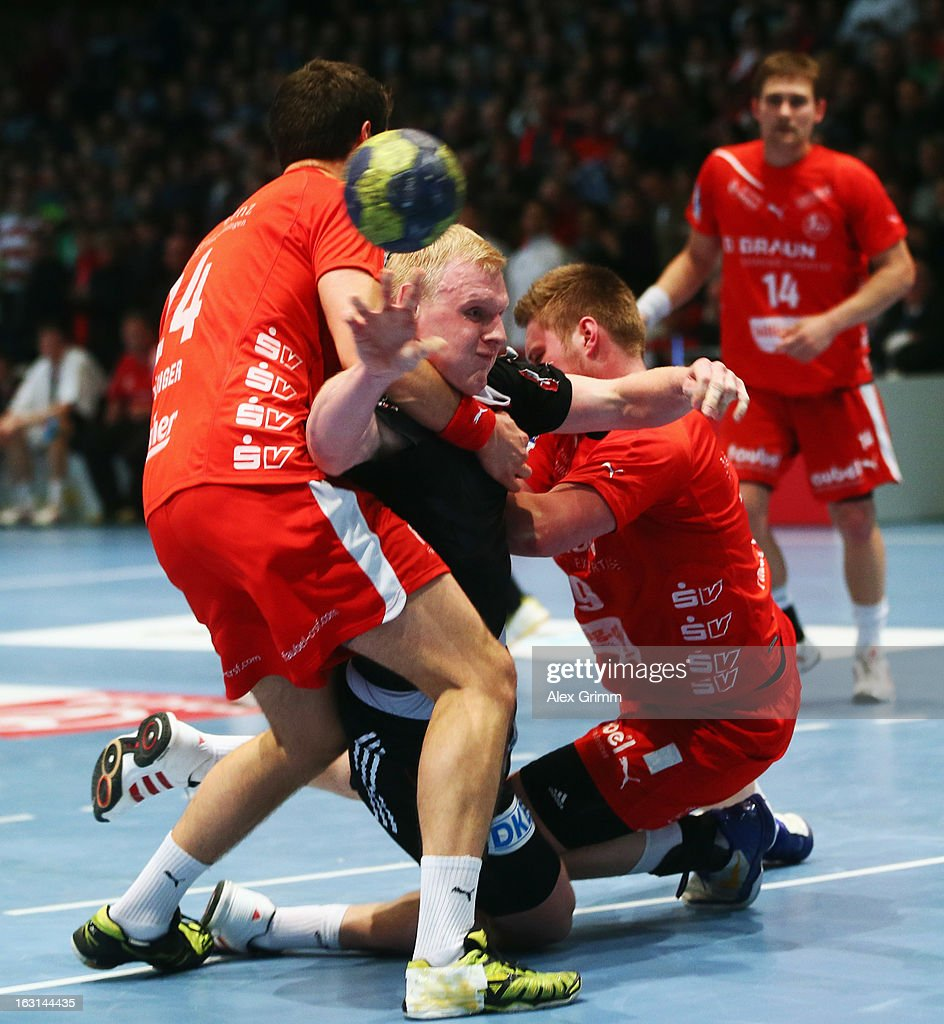 Patrick Wiencek (C) of Germany is challenged by Phil Raebinger (L) and Max Pregler of Melsungen during a benefit match between the German national handball team and MT Melsungen at Rothenbach-Halle on March 5, 2013 in Kassel, Germany.
