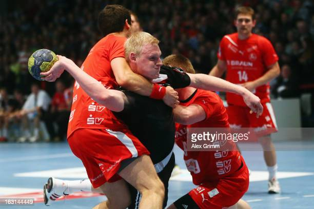 Patrick Wiencek of Germany is challenged by Phil Raebinger and Max Pregler of Melsungen during a benefit match between the German national handball...