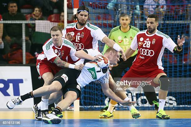 Patrick Wiencek of Germany is challenged by Szabolcs Zubai Laszlo Nagy and Szabolcs Szollosi of Hungary during the 25th IHF Men's World Championship...