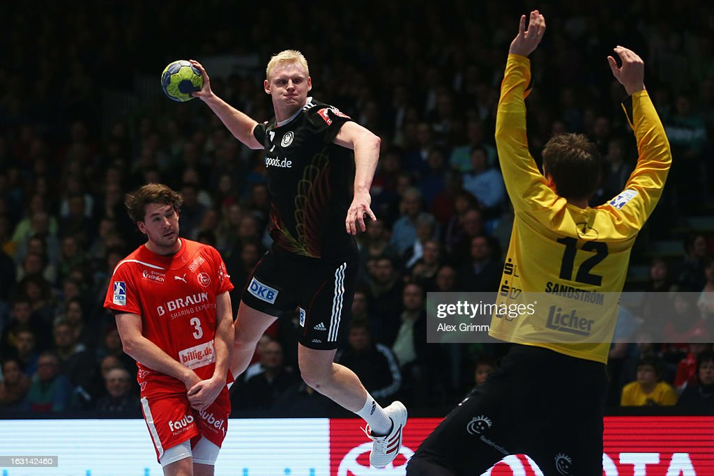 Patrick Wiencek (C) of Germany tries to score against goalkeeper <a gi-track='captionPersonalityLinkClicked' href=/galleries/search?phrase=Per+Sandstroem&family=editorial&specificpeople=2704493 ng-click='$event.stopPropagation()'>Per Sandstroem</a> and Jonathan Stenbacken of Melsungen during a benefit match between the German national handball team and MT Melsungen at Rothenbach-Halle on March 5, 2013 in Kassel, Germany.