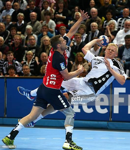 Patrick Wiencek of Kiel challenges for the ball with Michael Knudsen of Flensburg during the DKB Handball Bundesliga match between THW Kiel and SG...