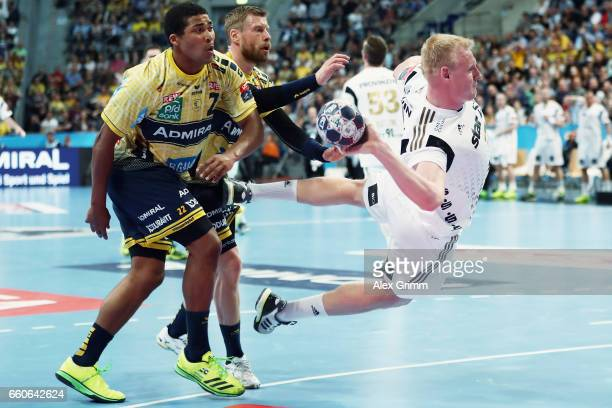 Patrick Wiencek of Kiel eludes Mads Mensah Larsen and Gudjon Valur Sigurdsson of RheinNeckar Loewen during the EHF Champions League Quarter Final Leg...