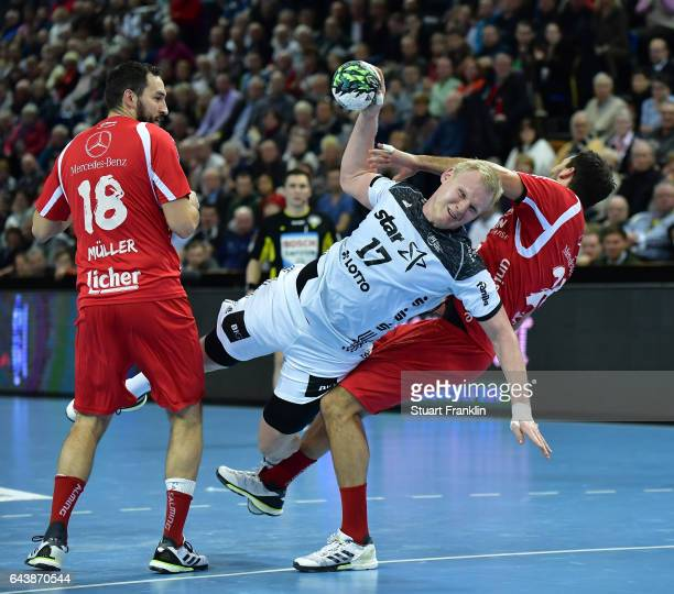 Patrick Wiencek of Kiel is challenged by Michael Mueller of Melsungen during the DKB Handball Bundesliga game between THW Kiel and MT Melsungen at...