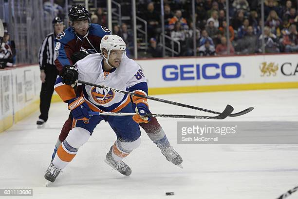 Patrick Wiercioch of the Colorado Avalanche pressures Nikolay Kulemin of the New York Islanders as he collects the puck during the third period at...