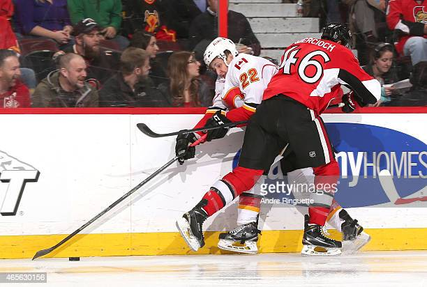 Patrick Wiercioch of the Ottawa Senators bodychecks Drew Shore of the Calgary Flames against the boards at Canadian Tire Centre on March 8 2015 in...