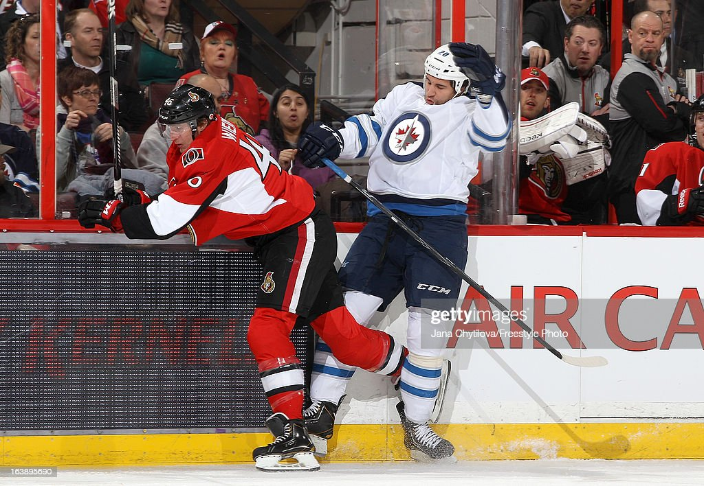 Patrick Wiercioch #46 of the Ottawa Senators checks Patrice Cormier #28 of the Winnipeg Jets along the boards, during an NHL game at Scotiabank Place, on March 17, 2013 in Ottawa, Ontario, Canada.
