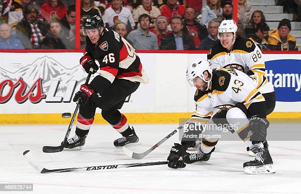Patrick Wiercioch of the Ottawa Senators feathers a pass against Matt Bartkowski and David Pastrnak of the Boston Bruins at Canadian Tire Centre on...