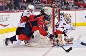 Patrick Wiercioch of the Ottawa Senators knocks down TJ Oshie of the Washington Capitals as he shoots on Andrew Hammond at the Verizon Center on...