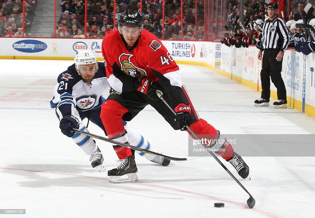 Patrick Wiercioch #46 of the Ottawa Senators skates the puck down low against T.J. Galiardi #21 of the Winnipeg Jets at Canadian Tire Centre on November 8, 2014 in Ottawa, Ontario, Canada.