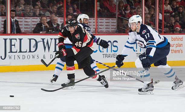 Patrick Wiercioch of the Ottawa Senators squeezes though Dustin Byfuglien and Adam Lowry of the Winnipeg Jets with the puck at the blue line at...
