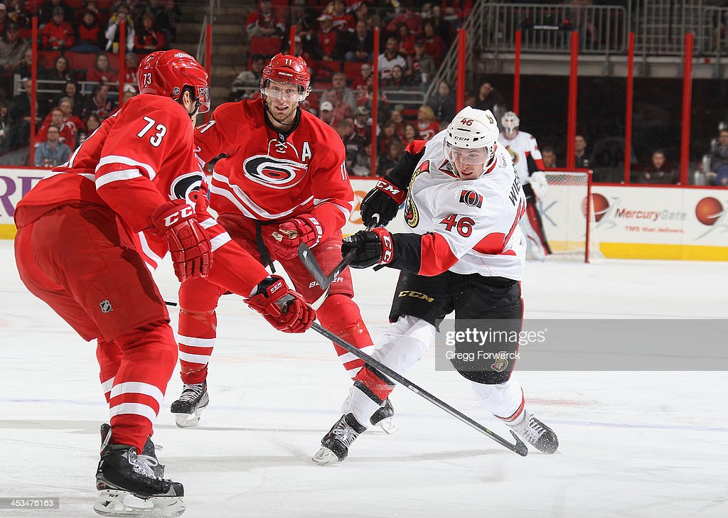 Patrick Wiercioch shoots the puck past Brett Bellemore of the Ottawa Senators during their NHL game at PNC Arena on November 24 2013 in Raleigh North...