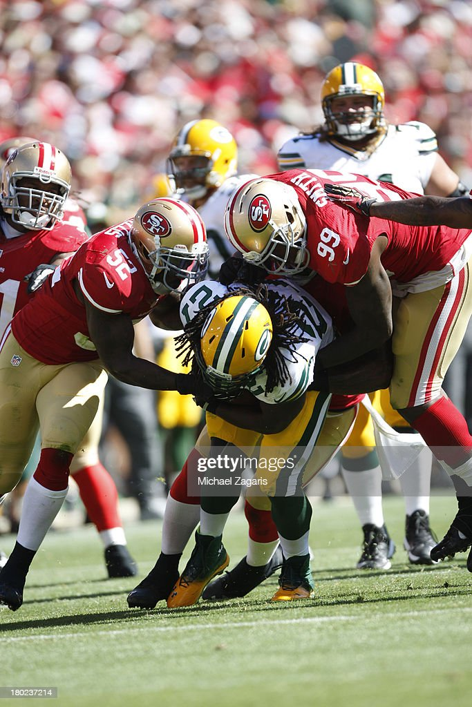 Patrick Willis #52 and Aldon Smith #99 of the San Francisco 49ers tackle Eddie Lacy #27 of the Green Bay Packers during the game at Candlestick Park on September 8, 2013 in San Francisco, California. The 49ers defeated the Packers 34-28.