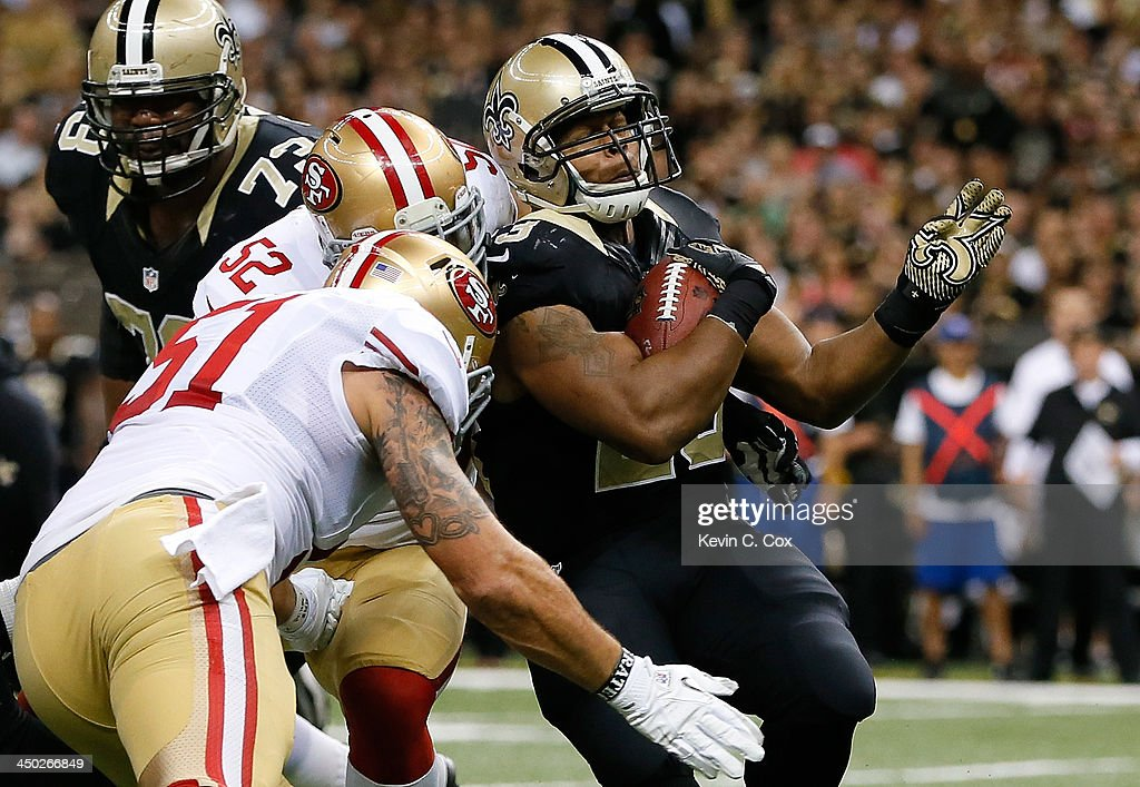 Patrick Willis #52 and Dan Skuta #51 of the San Francisco 49ers tackle Pierre Thomas #23 of the New Orleans Saints at Mercedes-Benz Superdome on November 17, 2013 in New Orleans, Louisiana.