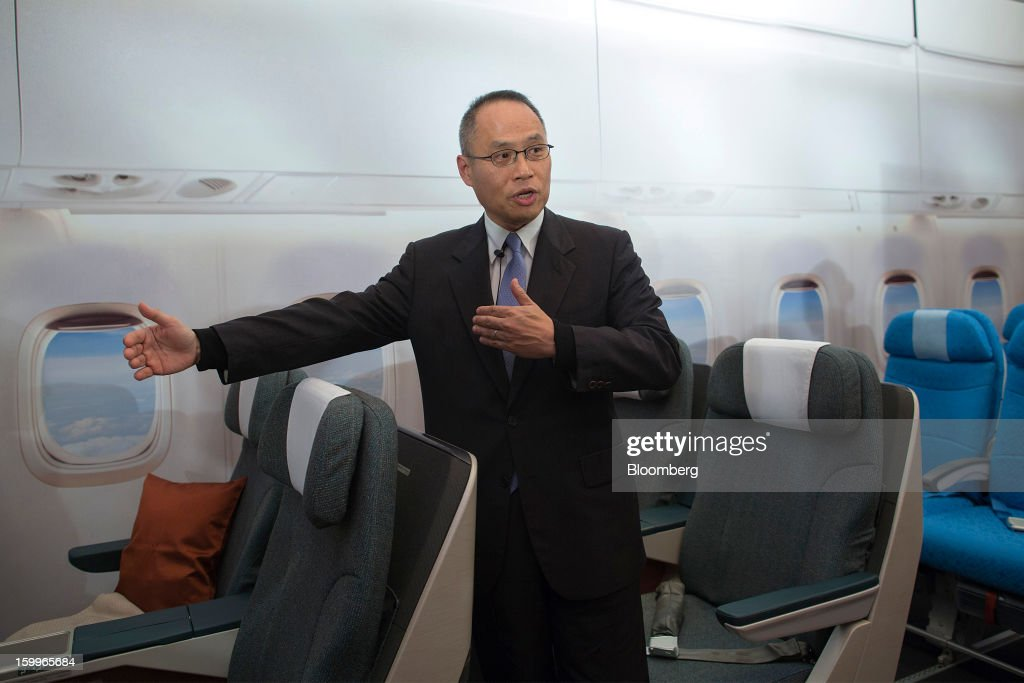 Patrick Yeung, chief executive officer of Hong Kong Dragon Airlines Ltd. (Dragonair), demonstrates the company's new business class seats, in green, and economy class seats, in blue, during a media briefing in Hong Kong, China, on Thursday, Jan. 24, 2013. Dragonair is to upgrade cabins and add new destinations this year. Photographer: Jerome Favre/Bloomberg via Getty Images