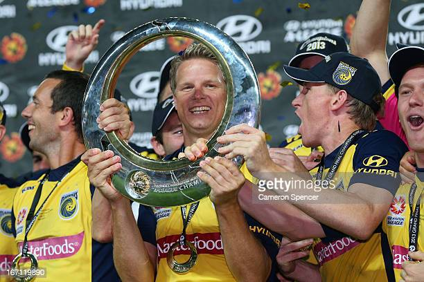 Patrick Zwaanswijk of the Mariners and team mates celebrate with the trophy after winning the ALeague 2013 Grand Final match between the Western...