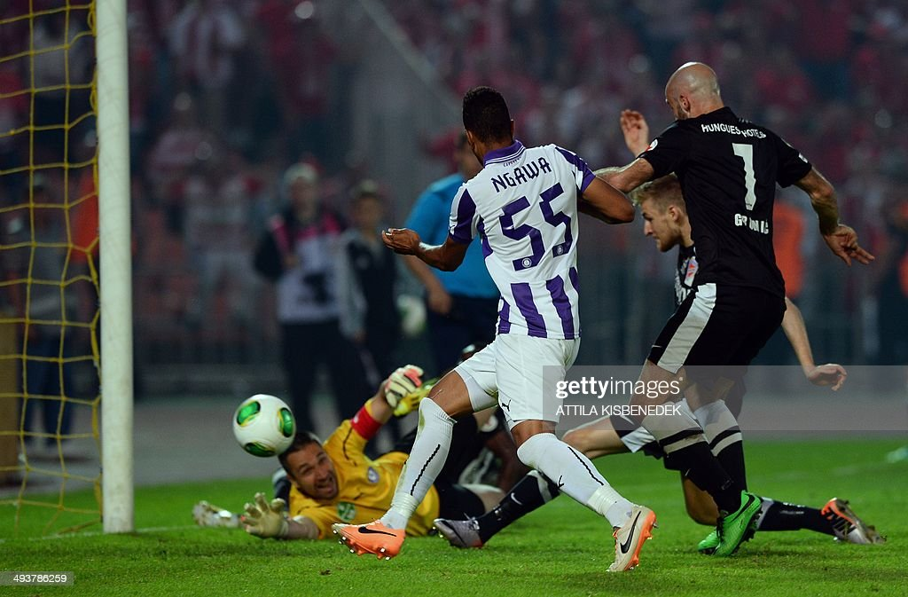 Patrik Bacs (C) of VTK Disosgyor scores a goal past TE Ujpest's goalkeeper Szabolcs Balajcza (L) during the Hungarian Cup final football match VTK Disosgyor vs TE Ujpest on May 25, 2014 at the Puskas stadium in Budapest.