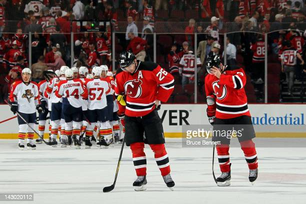 Patrik Elias and Zach Parise of the New Jersey Devils skate off the ice dejected as the Florida Panthers celebrate winning 43 in Game Three of the...