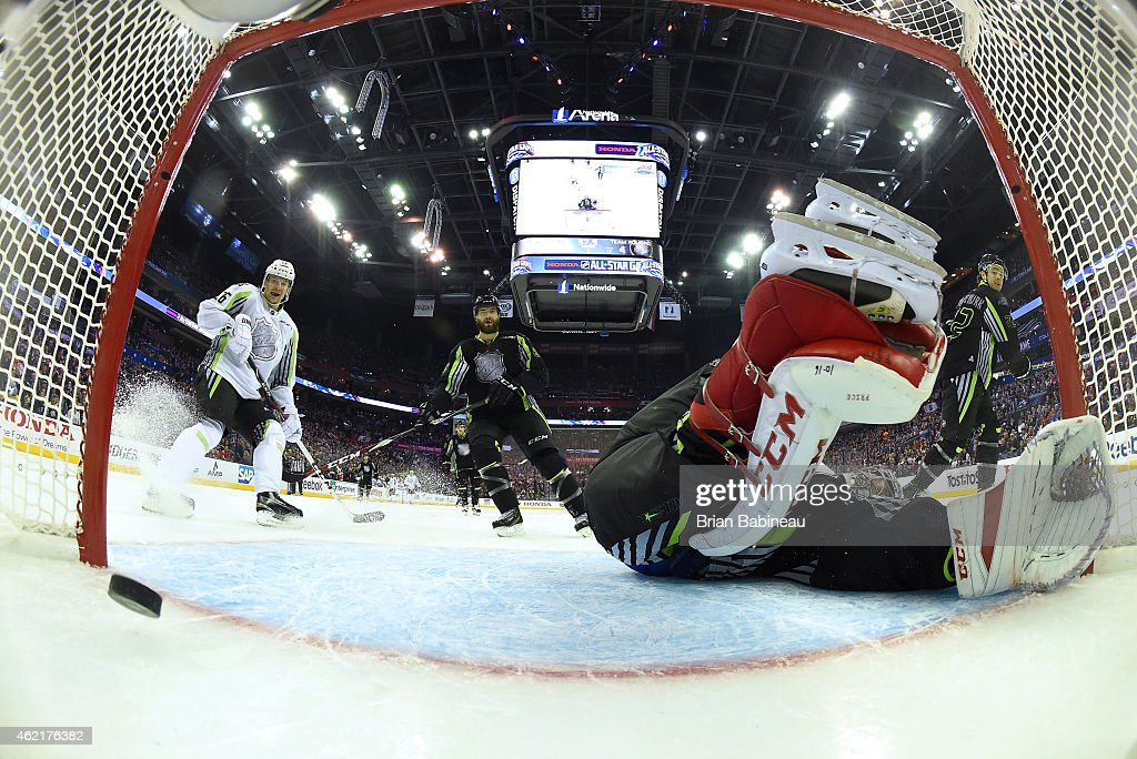 Patrik Elias of the New Jersey Devils and Team Toews and Brent Burns of the San Jose Sharks and Team Foligno watch the puck go into the net on a goal...