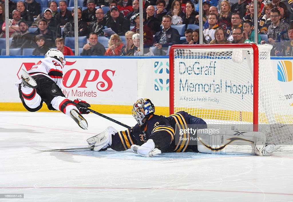Patrik Elias #26 of the New Jersey Devils is sent flying as he is stopped on a shootout attempt against Ryan Miller #30 of the Buffalo Sabres on April 7, 2013 at the First Niagara Center in Buffalo, New York. Buffalo defeated New Jersey, 3-2.
