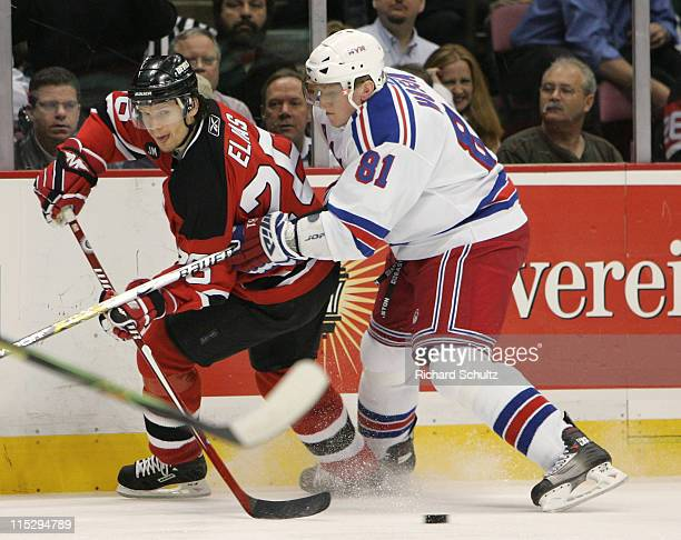 Patrik Elias of the New Jersey Devils passes the puck as New York Rangers' Marcel Hossa defends during the first period of game two in the first...