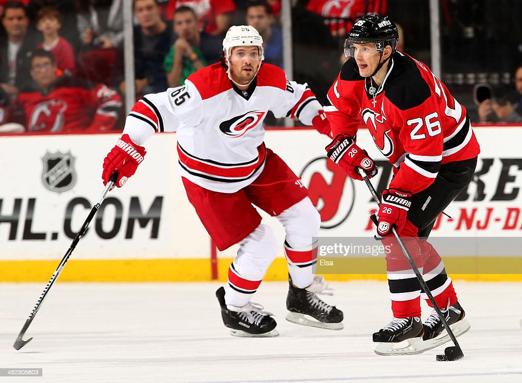 Patrik Elias #26 of the New Jersey Devils passes the puck as Ron Hainsey #65 of the Carolina Hurricanes defends at Prudential Center on November 27, 2013 in Newark, New Jersey.The Carolina Hurricanes defeated the New Jersey Devils 4-3.