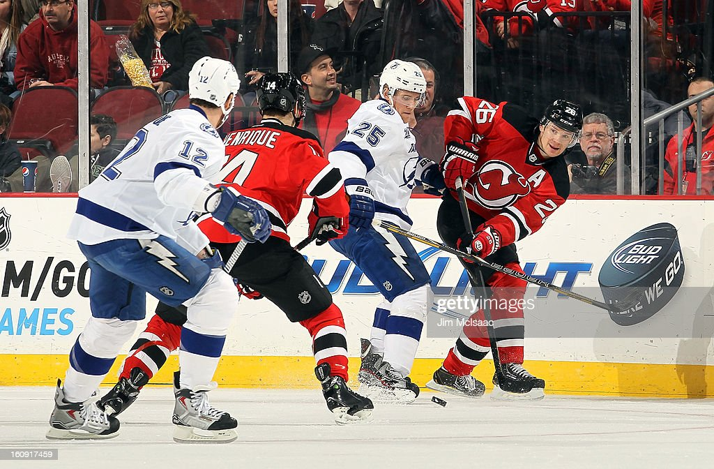 Patrik Elias #26 of the New Jersey Devils passes the puck to teammate Adam Henrique #14 as Matt Carle #25 and Ryan Malone #12 of the Tampa Bay Lightning defend at the Prudential Center on February 7, 2013 in Newark, New Jersey.
